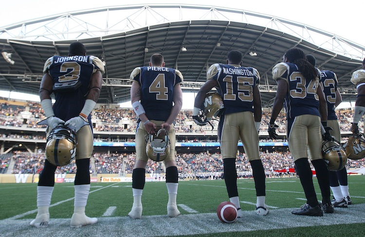 Winnipeg Blue Bombers stand for the national anthem before the game. (JOE BRYKSA / WINNIPEG FREE PRESS)
