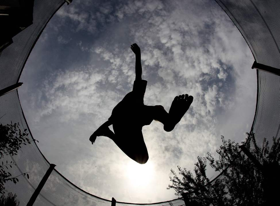 A boy jumps on a trampoline in a garden in Frankfurt, Germany on a warm and humid day. (AP Photo/Michael Probst)