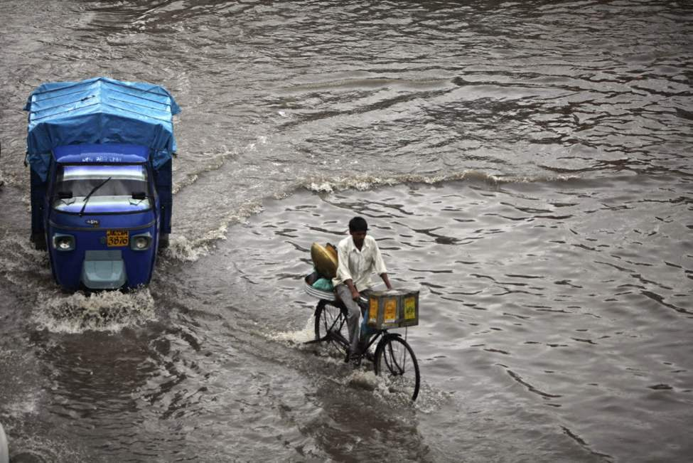 A man rides his bicycle through a waterlogged street during a monsoon shower in Jammu, India. The monsoon rains which usually hit India from June to September are crucial for farmers whose crops feed hundreds of millions of people. (AP Photo/Channi Anand)