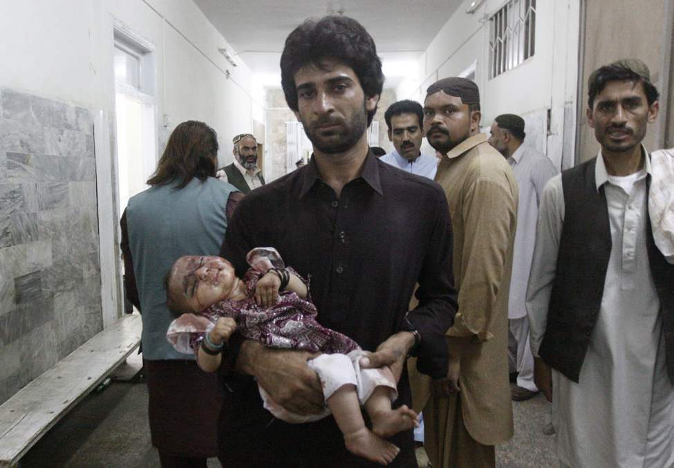 A man brings an injured child to a local hospital in Quetta, Pakistan. Police say a roadside bomb targeting a security convoy has killed at least one civilian and wounded several others in southwestern Pakistan. (AP Photo/Arshad Butt)