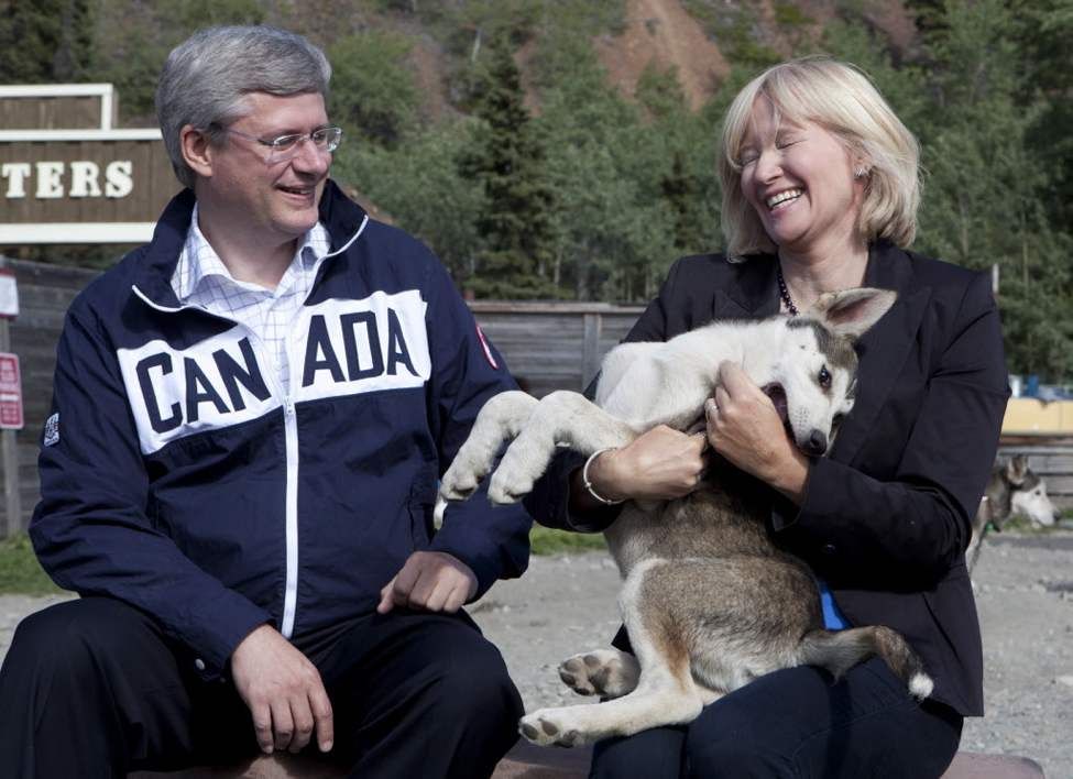 Laureen Harper laughs as she holds a husky with Canadian Prime Minister Stephen Harper as they tour Caribou Crossing, Yukon, south of Whitehorse . (The Canadian Press / Adrian Wyld)
