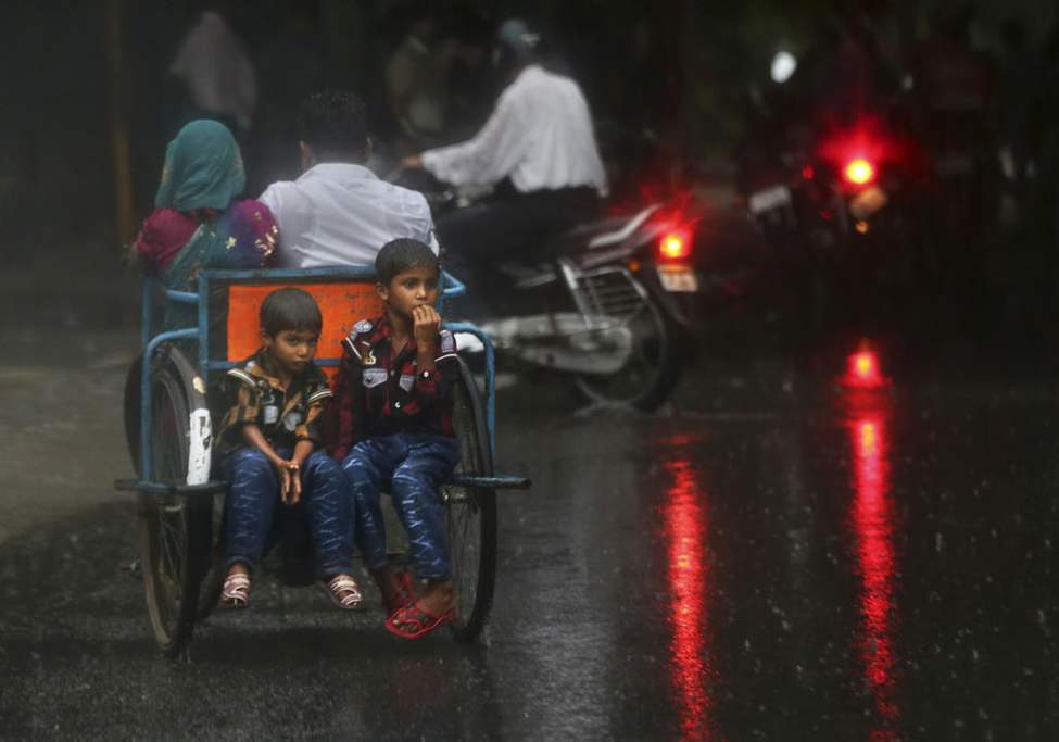 Indian boys catch a ride on the back of a man's wheelchair during a sudden monsoon rain shower in New Delhi, India. The showers, which normally run from June to September, are crucial in a country where 60 per cent of the population works in agriculture and less than half the farmland is irrigated.(AP Photo/Kevin Frayer)
