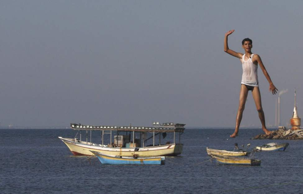 A Palestinian youth jumps into the Mediterranean sea on the beach at the port of Gaza City, Gaza. (AP photo/Hatem Moussa)