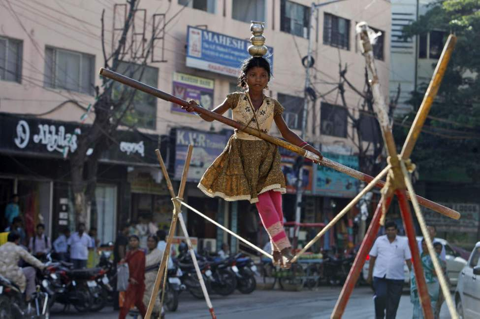 An Indian child street artist walks a tightrope in Hyderabad, India. The Indian cabinet has cleared a proposal that makes employment of children below 14-years old an offence with a maximum three years imprisonment or fine up to rupees 50,000 (US$909), according to news reports. The meeting presided by the Prime Minister also approved to raise the blanket ban on employing children in hazardous industries like mining from 14 to 18. (AP Photo/Mahesh Kumar A.)