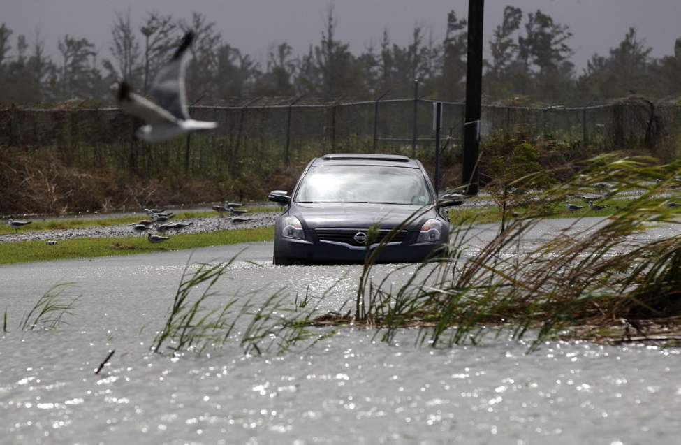 A car sits stranded in rising floodwaters from Isaac, which is expected to make landfall in the region as a hurricane this evening in Venice, La., the southernmost tip of the state. Venice is outside the storm protection system and has been under mandatory evacuation. Forecasters at the National Hurricane Center warned that Isaac, especially if it strikes at high tide, could cause storm surges of up to 12 feet (3.6 meters) along the coasts of southeast Louisiana and Mississippi and up to 6 feet (1.8 meters) as far away as the Florida Panhandle. (AP Photo/Gerald Herbert)