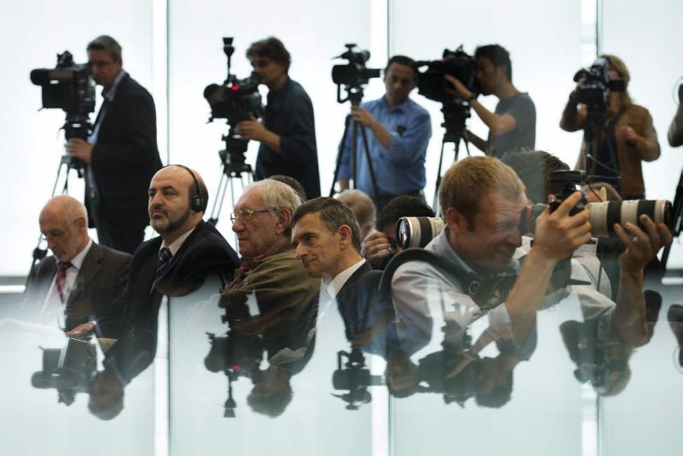 Partially reflected in a glass shelf, journalists cover a news conference of members of Syrian opposition groups presenting the program of the project 'The Day After: Supporting a democratic transition in Syria', in Berlin. (AP Photo/Markus Schreiber)