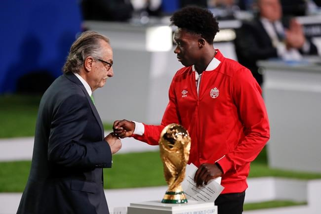 Decio de Maria, President of the Football Association of Mexico, left, and Canadian soccer player Alphonso Davies, right, present a joint United bid to host the 2026 World Cup at the FIFA congress.