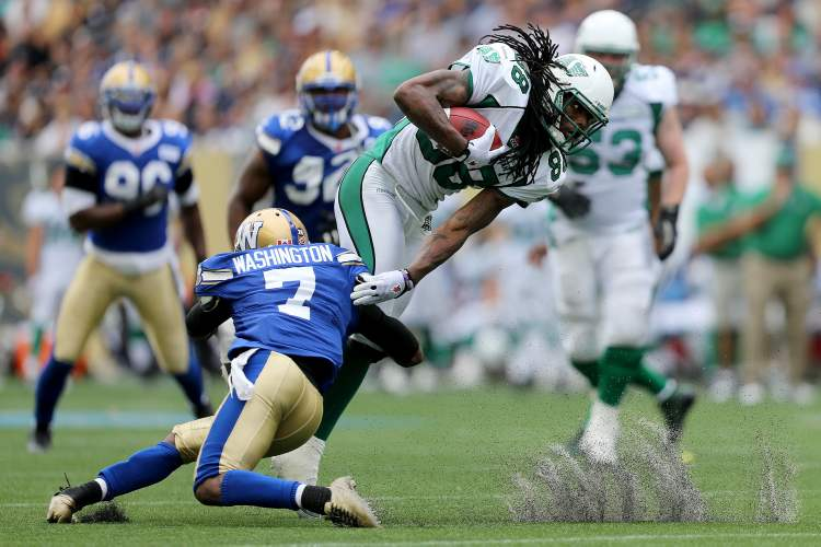 Winnipeg Blue Bomber Demond Washington (7) brings down Saskatchewan Roughrider Taj Smith (88) during the first half of the Banjo Bowl Sunday. (Trevor Hagan / Winnipeg Free press)
