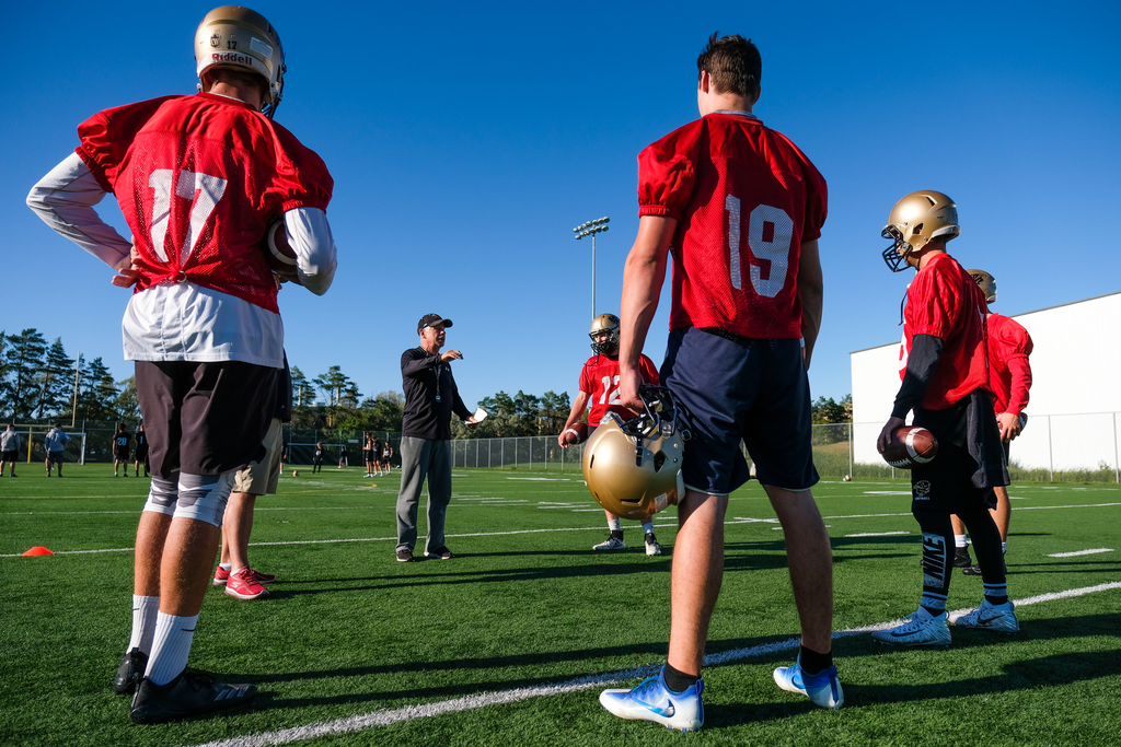 University of Manitoba Bisons football team coach Brian Dobie, centre, maintains social distance while he speaks with his quarterbacks during practice.