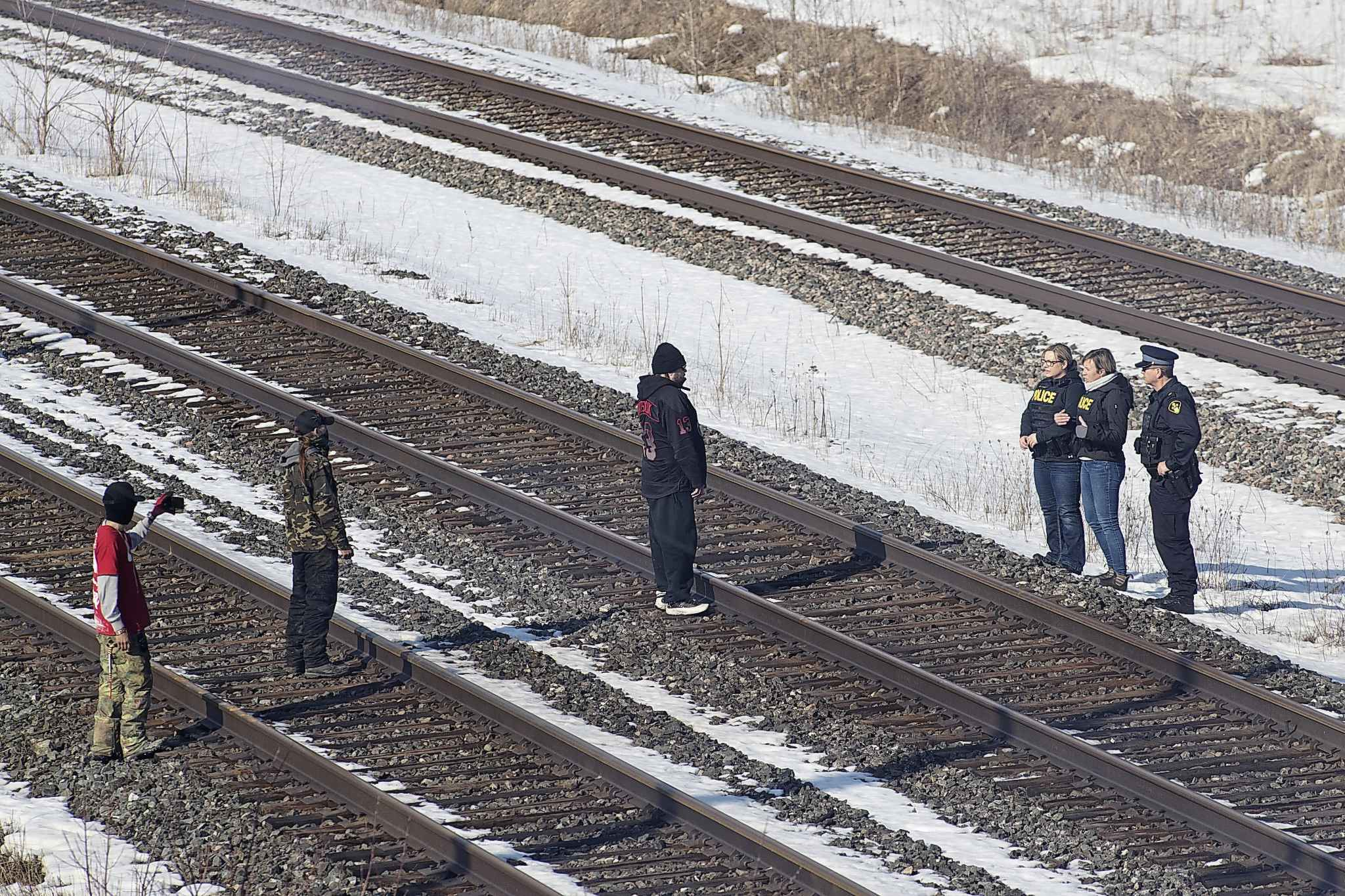 Ontario Provincial Police liaison officers speak with protesters on the closed train tracks at a second rail blockade in Tyendinaga Mohawk Territory, near Belleville, Ont., on Monday. THE CANADIAN PRESS/Lars Hagberg