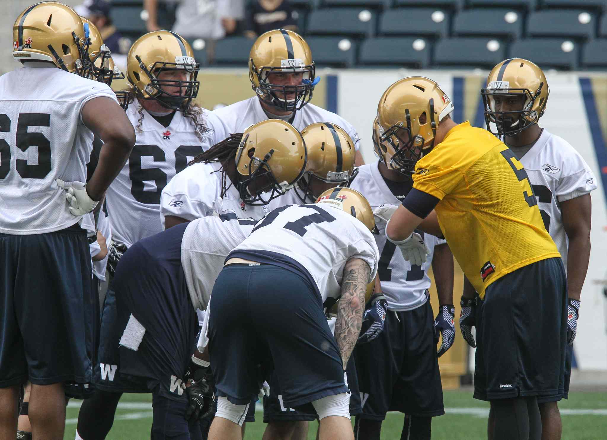 Quarterback Drew Willy (in yellow jersey) in the huddle during the first official day of the Winnipeg Blue Bombers training camp at Investors Group Field Sunday morning.