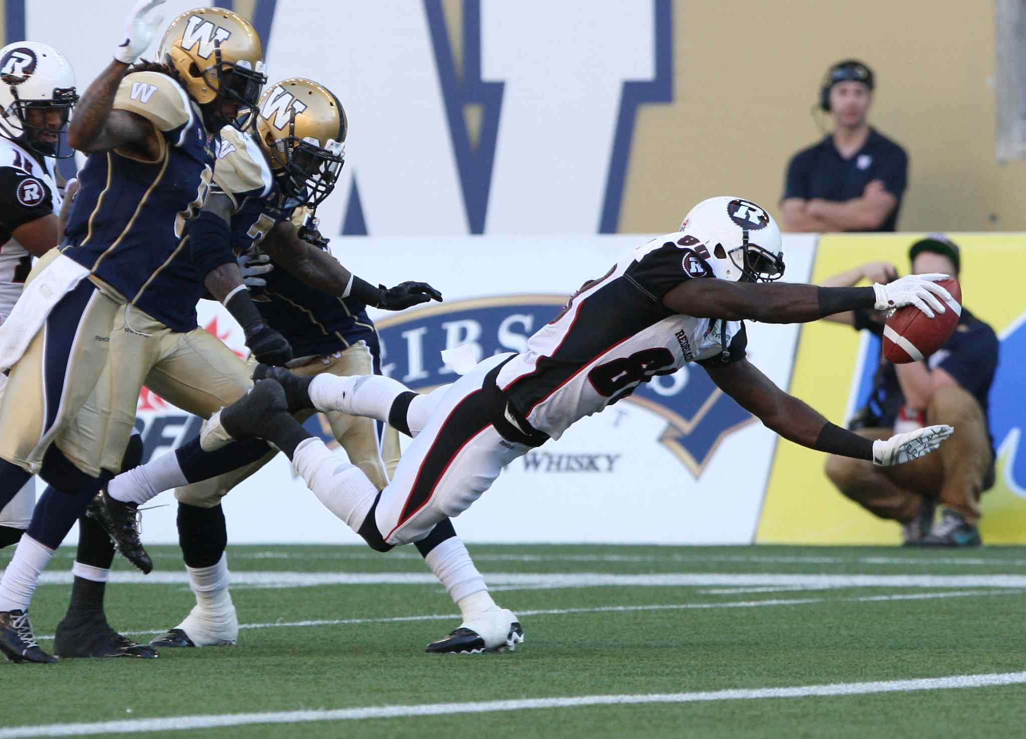 Winnipeg Blue Bombers could only watch as Ottawa Redblacks' Dobson Collins dives in for a first-quarter touchdown during CFL action at Investors Group Field in Winnipeg Thursday night.