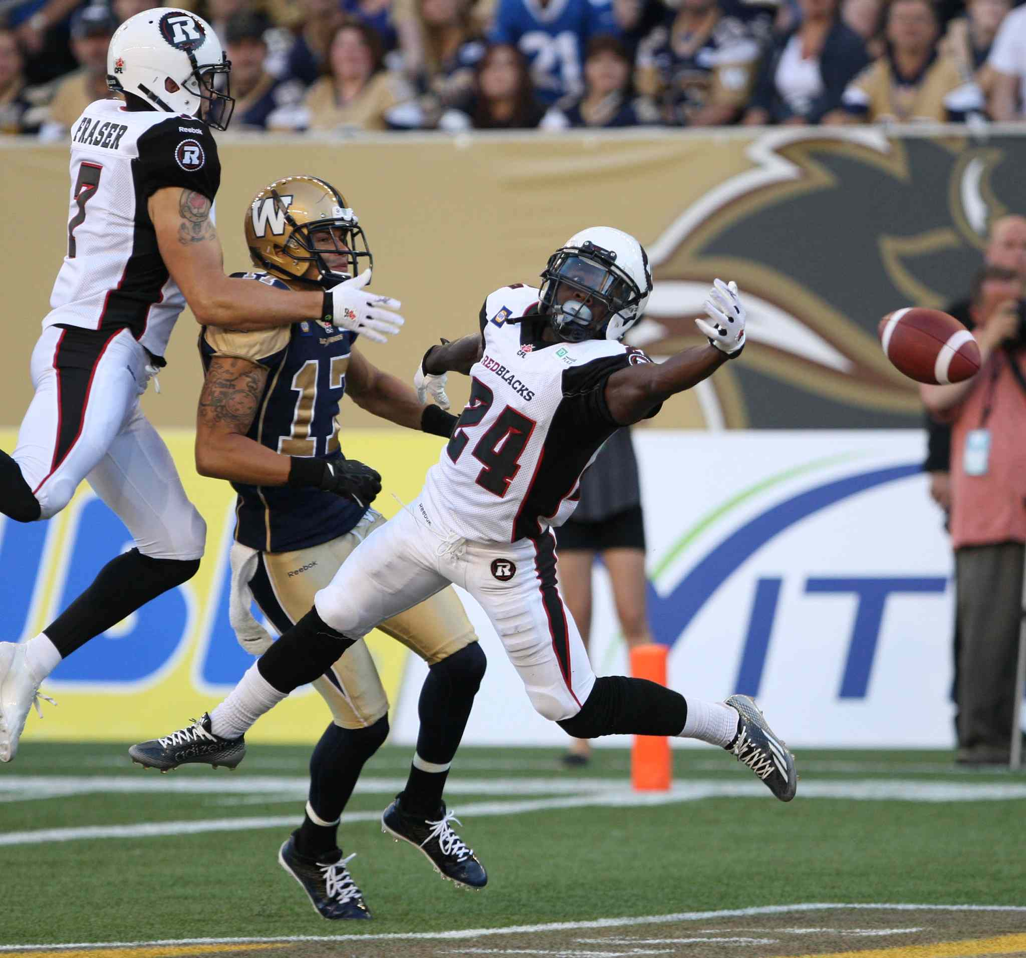 Winnipeg Blue Bombers' Nick Moore is surrounded by Ottawa Redblacks' Eric Frazer, left, and Jerell Gavins in the end zone during first half of Winnipeg's game.