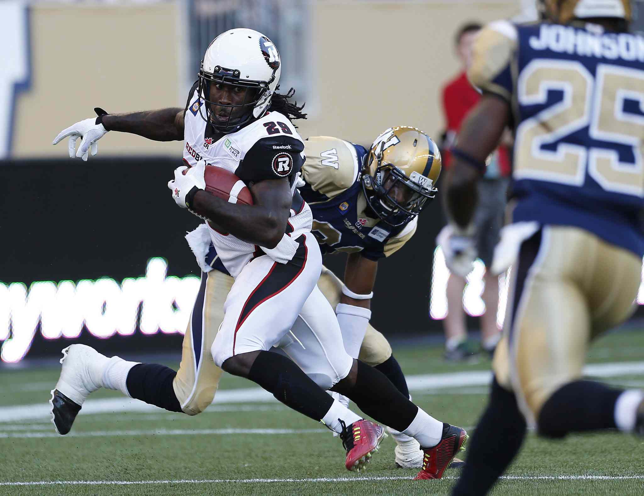 Ottawa Redblacks' Chevon Walker (29) breaks the tackle by Winnipeg Blue Bombers' Maurice Leggett (31) and runs the ball in for the touchdown during the first half of CFL action in Winnipeg on Thursday.
