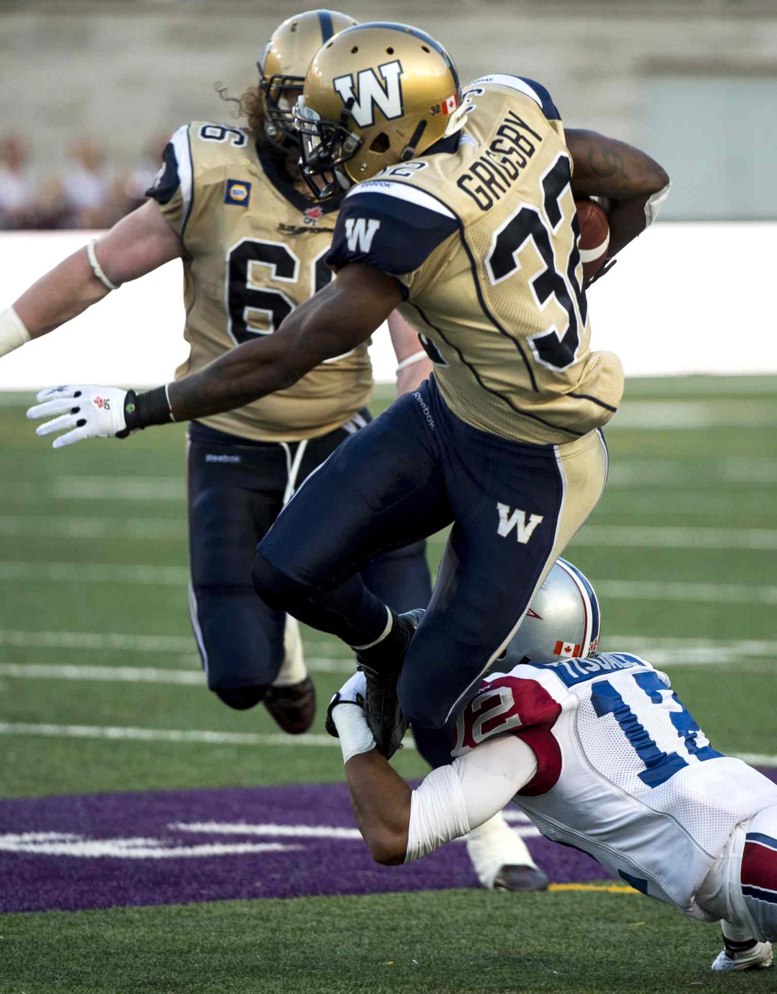 Winnipeg Blue Bombers' running back Nic Grigsby is tackled Montreal Alouettes' cornerback Geoff Tisdale during the second quarter.