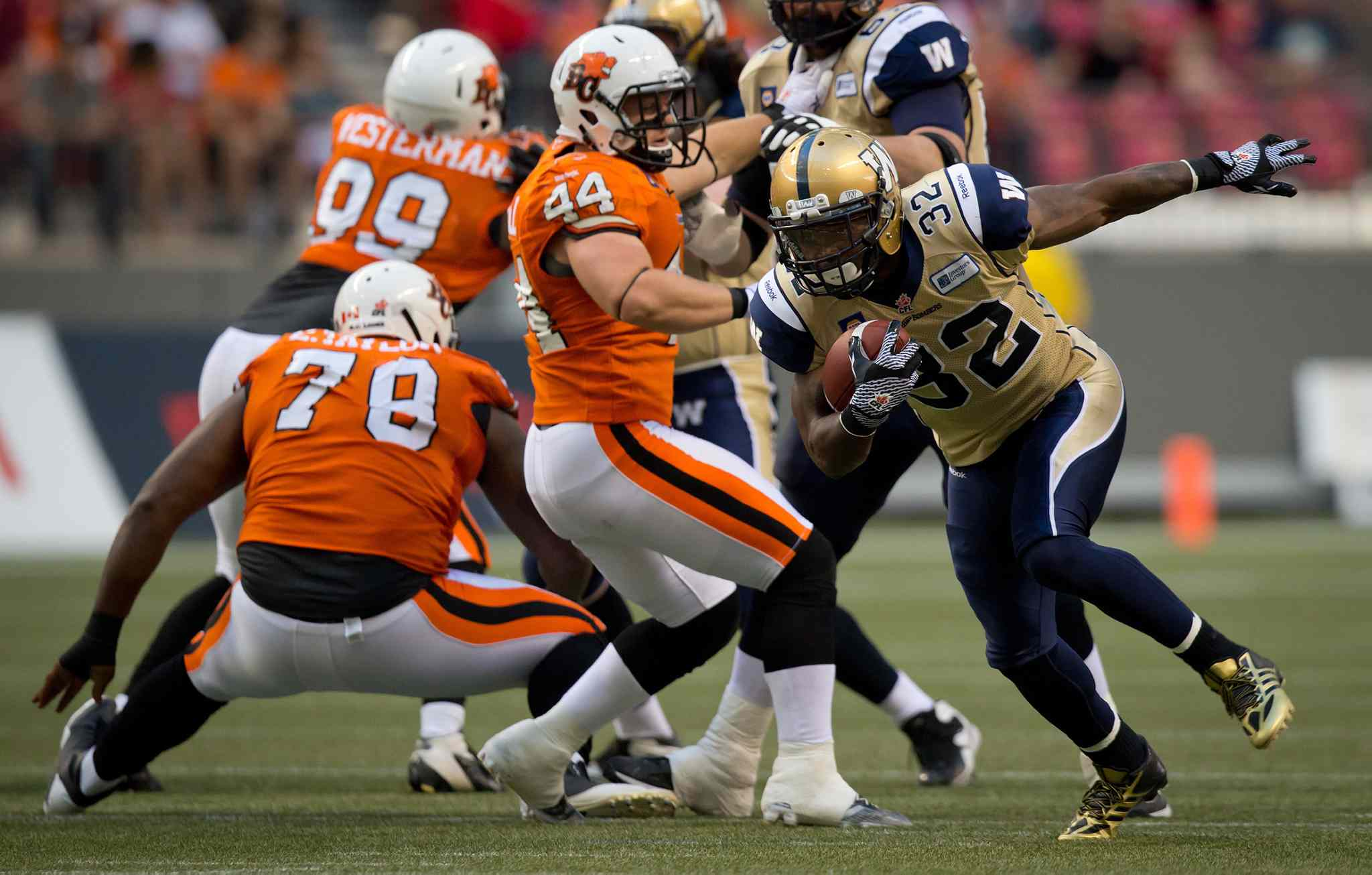 Winnipeg Blue Bombers' Nic Grigsby (32) runs the ball past B.C. Lions' Adam Bighill (44) during the first half of Friday's game.