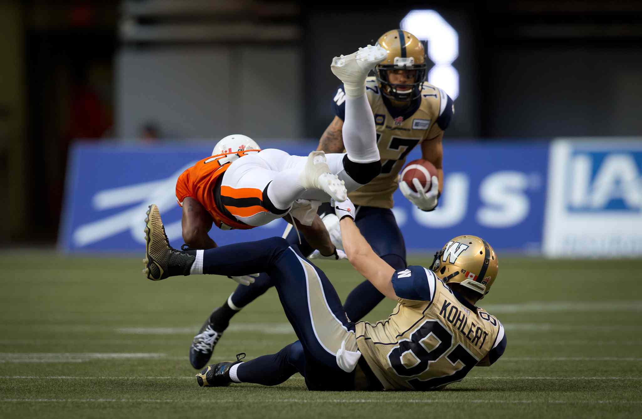 B.C. Lions' Dante Marsh, left, collides with Winnipeg Blue Bombers' Rory Kohlert, bottom, as Nick Moore, back, carries the ball during the first half of Friday's game.
