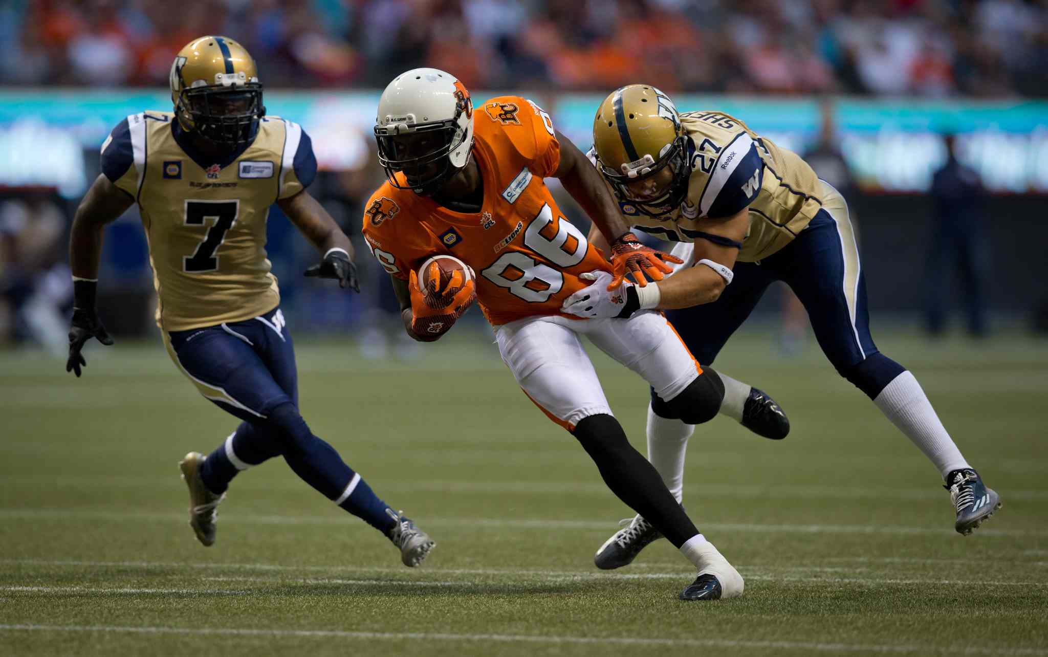 B.C. Lions' Courtney Taylor, centre, is grabbed by Winnipeg Blue Bombers' Teague Sherman, right, as Demond Washington, left, trails the play during the first half of Friday's game.