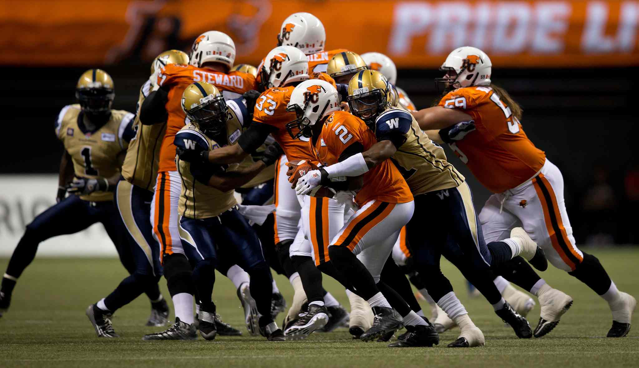 Winnipeg Blue Bombers' Maurice Leggett, second right, sacks B.C. Lions' quarterback Kevin Glenn (2) during the second half of Friday's game.
