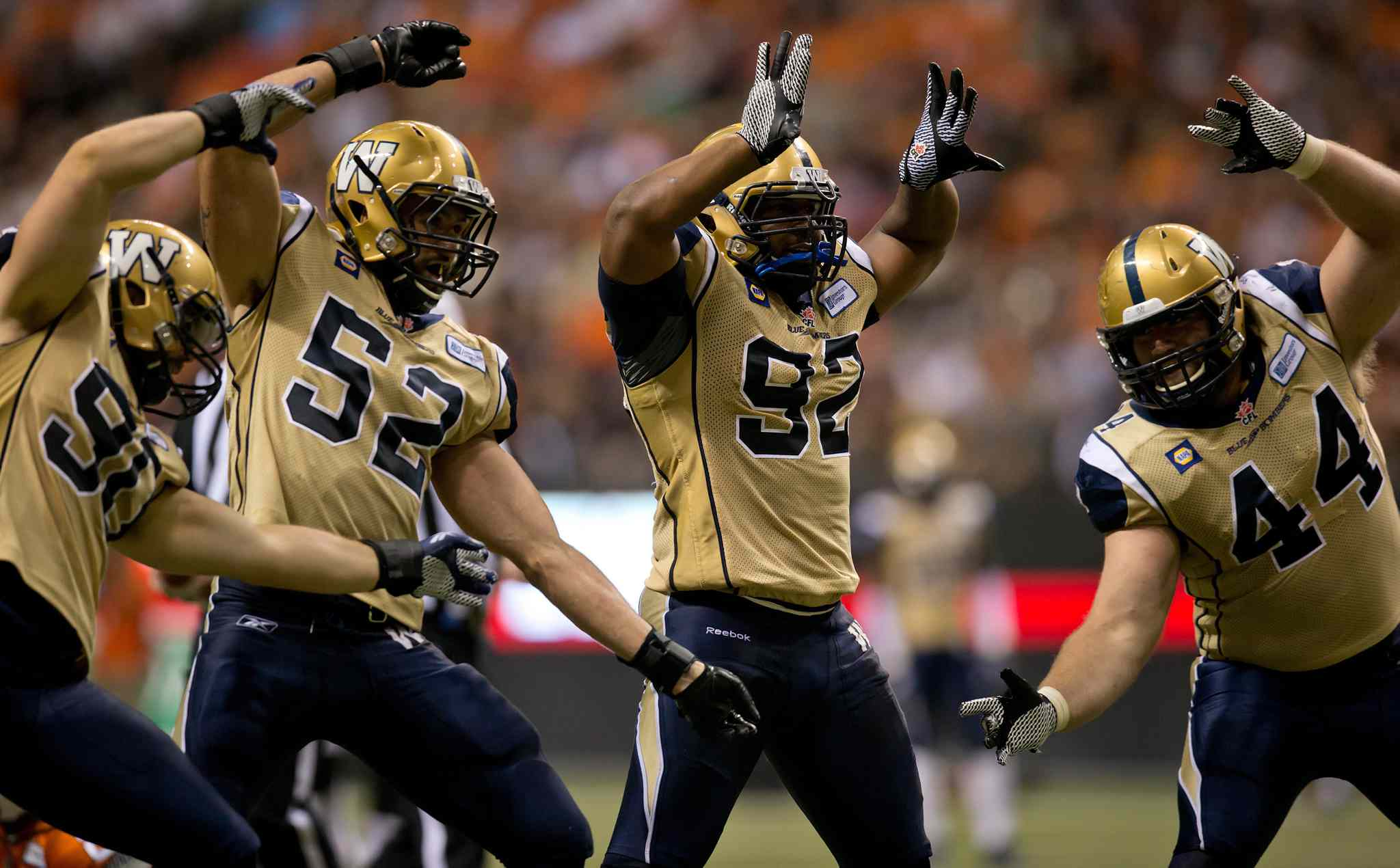 Winnipeg Blue Bombers' Greg Peach, from left to right, Louie Richardson, Bryant Turner Jr. and Zach Anderson celebrate after Turner sacked B.C. Lions' quarterback Kevin Glenn during the second half of a CFL football game in Vancouver, B.C., on Friday July 25, 2014.