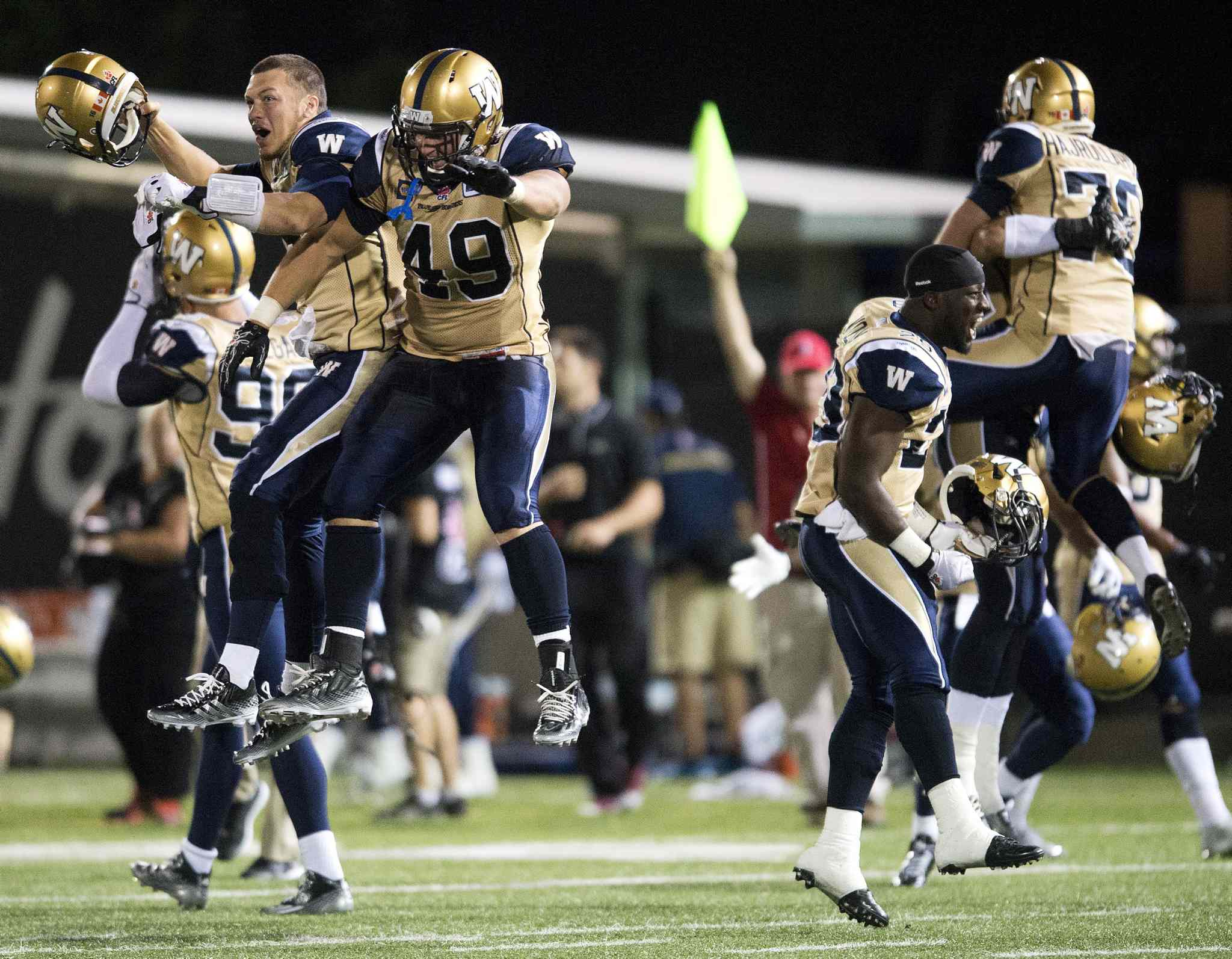 Winnipeg Blue Bombers' Robert Marve, left, and Mike Cornell, right, celebrate after defeating the Hamilton Tiger-Cats.