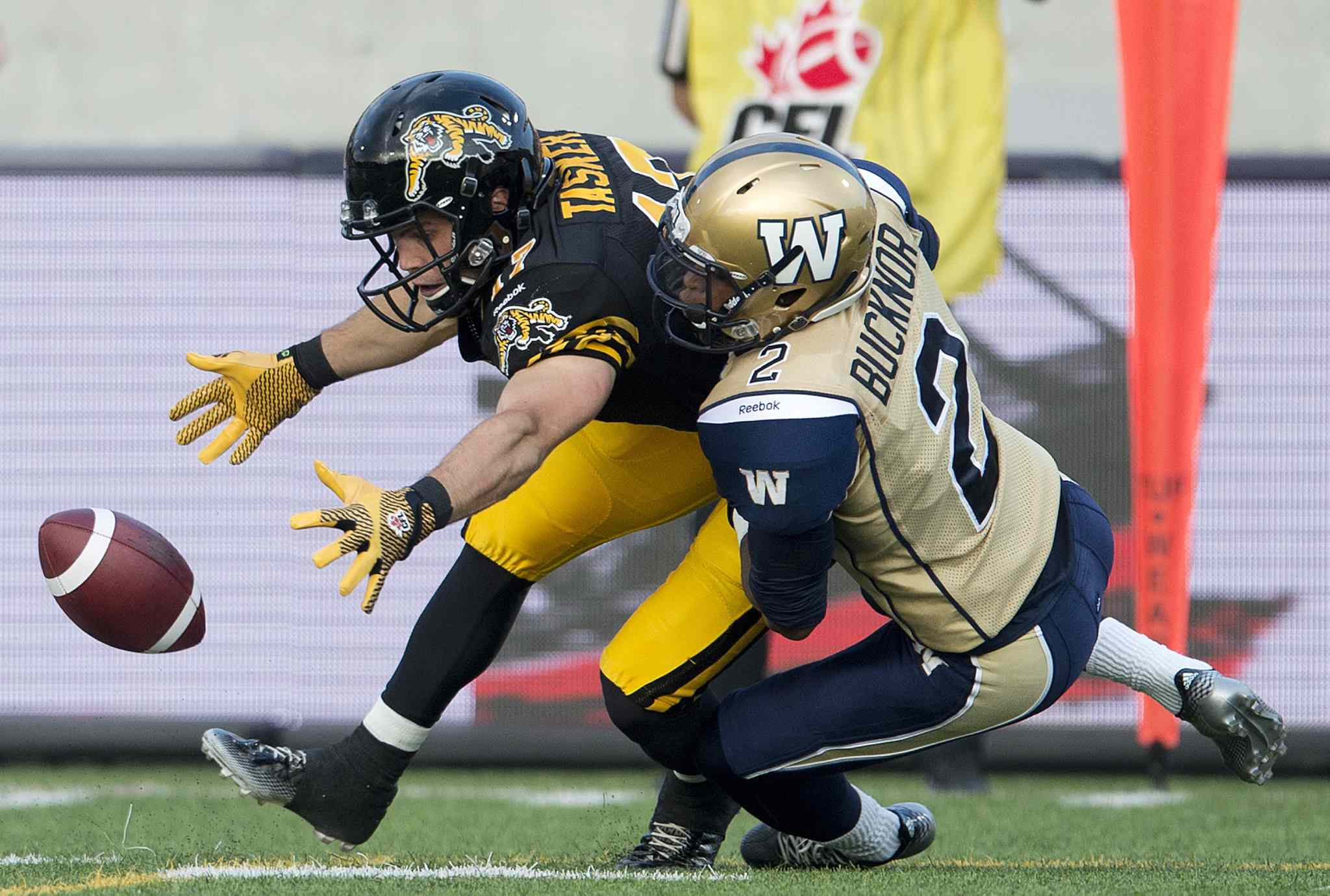 Hamilton Tiger-Cats' receiver Luke Tasker, left, loses the ball but recovers it past Winnipeg Blue Bombers' defensive back Matt Bucknor, right, during the first half of Thursday's game.