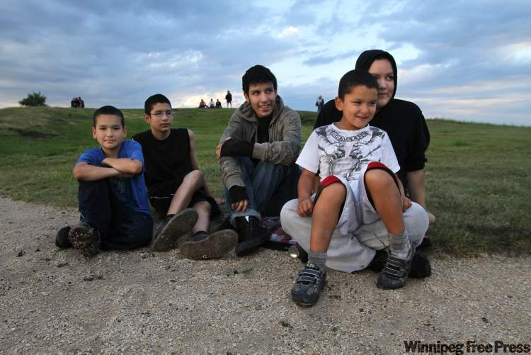 Jeremy Swan, 11, (from left) Leon Green, 13, Eric Ducharme, 17, Gary Kirton, 7, and Tanya Ducharme, 18, watch from Garbage Hill.