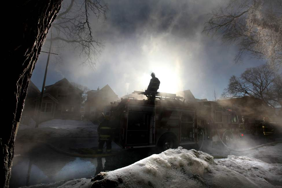A firefighter is silhouetted against the mist in the air stands  while beginning to clean up after a house fire at  394 Home Street Saturday morning.  February 26, 2011