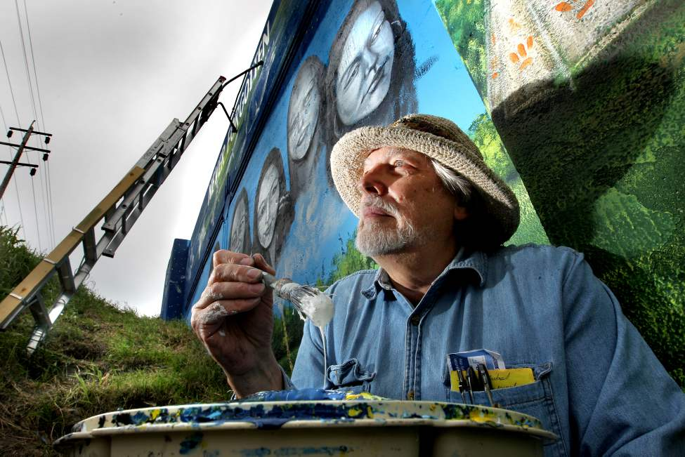 Artist Tom Andrich sits next to one of his latest murals. He is putting the finishing touches on his Empress Street overpass mural of missing Aboriginal women with the title