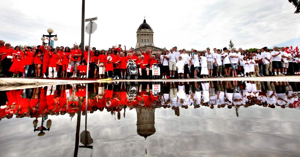 Thousands of Winnipeggers are reflected in a large puddle of water  from an early morning rain while gathering at the Legislative grounds Friday as part of Canada Day Celebrations.  