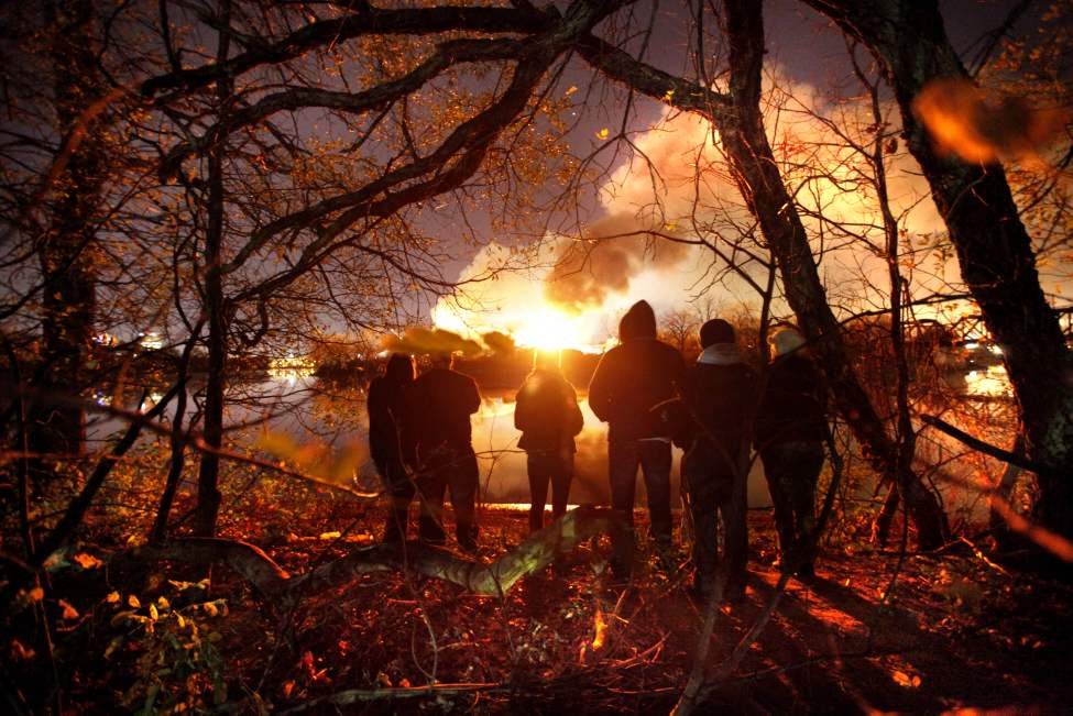 Friends gather to watch a large industrial fire in Point Douglas Wednesday night across the street along the Red River off Archibald Street. 