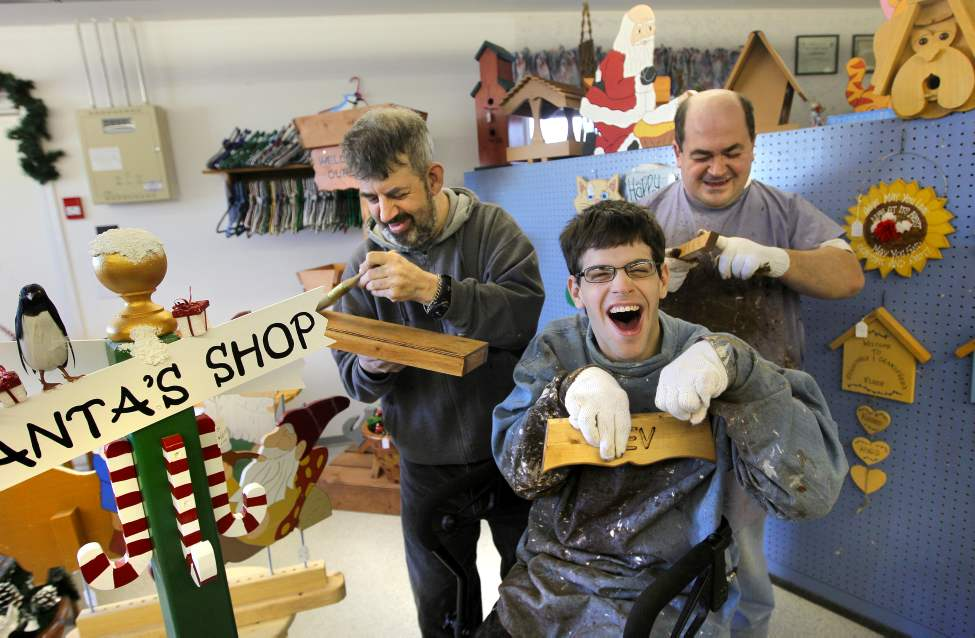 Mentally handicapped adults are all smiles as they work extra hard at this time of year finishing Christmas orders at Mountain Industries in rural Manitoba.  The shop, located in Notre Dame Du Lourdes, a small town west of the city, makes everything from small tables and chairs, miniature barns and houses to knitted products like rugs. Gilbert, Daryl and Justin show off some of their works.