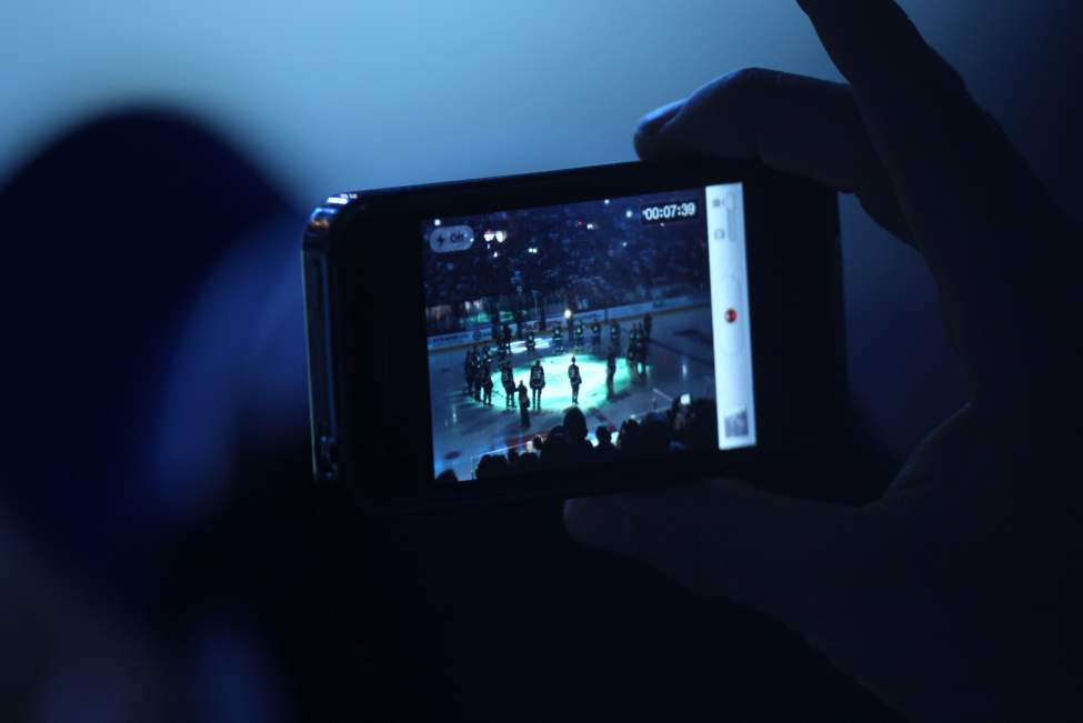 A fan records the opening ceremonies as the Winnipeg Jets take on the Montreal Canadiens in the NHL regular season home opener at the MTS Centre. October 9, 2011