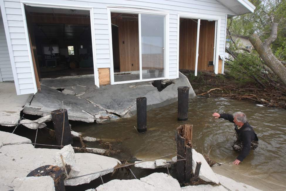 Delta Beach, Manitoba-   Rick Henderson wades through water at a cottage that had its cement deck and insides ripped out at East Delta Beach Thursday. High winds whipped up the already-flooded Lake Manitoba Tuesday afternoon and destroyed many cottages and homes in the area.