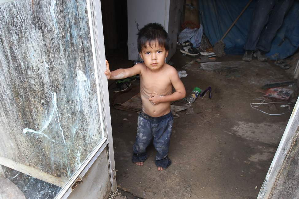A child peers from the front doorway of Richard Andrews' trailer in Wasagamack First Nation.  It is in filthy condition, has mould, and is overpopulated by over 13 people living inside. It has no running water.  August 18, 2011