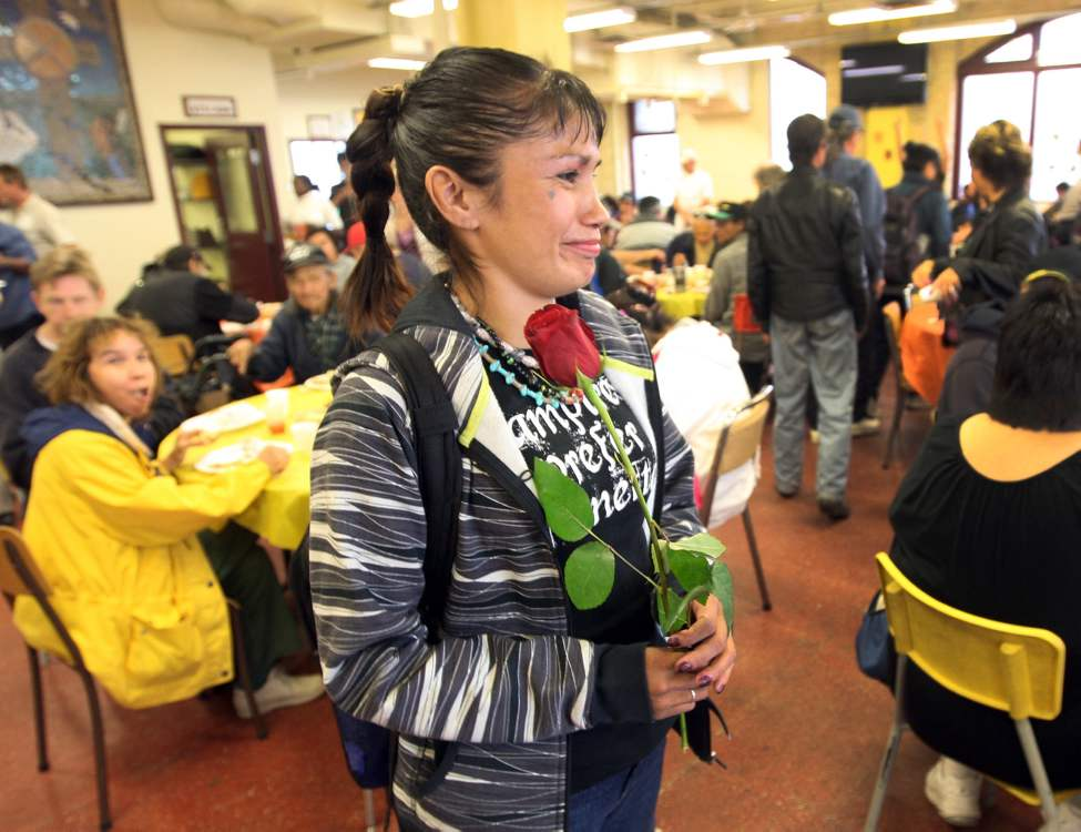 A lady known as Yolanda holds a rose after eating at the annual turkey dinner Thanksgiving Monday at Siloam Mission in Winnipeg. Bouquets of flowers from an anonymous donor were given to those who attended.