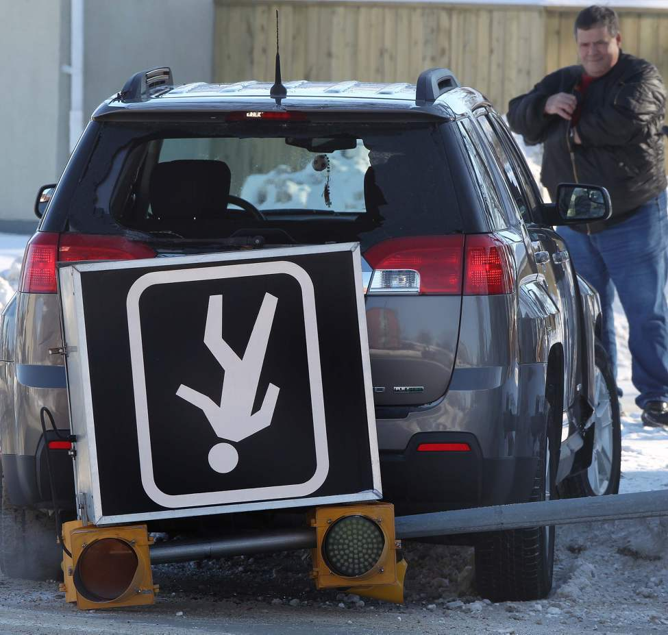 Winter Driving - A man looks at his vehicle on Regent Ave West and Moroz Street. No one was injured, but a large pedestrian corridor sign was knocked to the ground in the mishap. January 16, 2013   (JOE BRYKSA / WINNIPEG FREE PRESS)