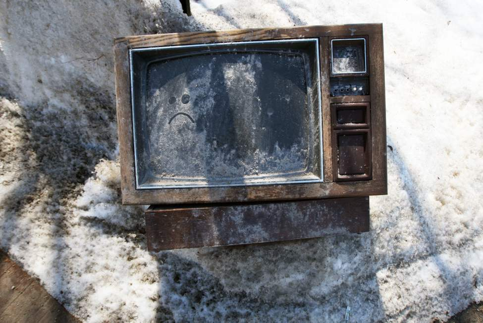 Turned off- An expired television sits in a snow bank in the back alley of Mountain Avenue. April 19, 2013   (JOE BRYKSA / WINNIPEG FREE PRESS)