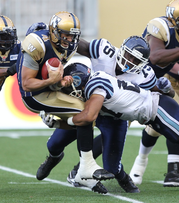 Winnipeg Blue Bombers quarterback Buck Pierce gets sacked by Shane Horton (centre) and Jonathan Williams late in the second quarter. (Tim Krochak / Halifax Chronicle / Special to the Winnipeg Free Press)