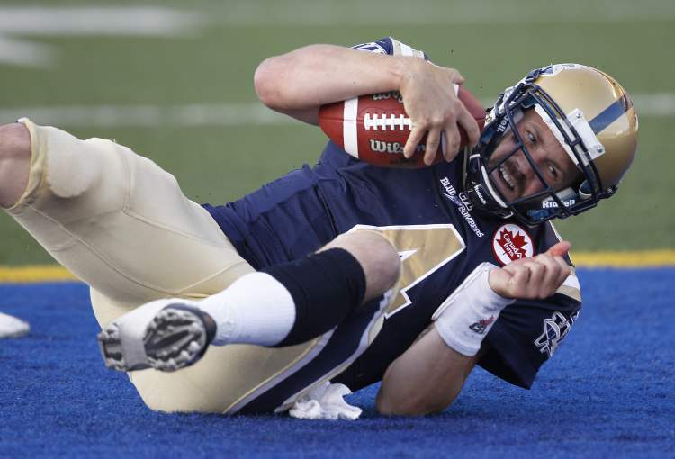 Buck Pierce falls into the end-zone after scrambling a long touchdown run late in the first half of CFL action at Canad Inns Stadium.