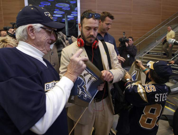 Buck Pierce and Doug Brown signed autographs for fans after arriving back in Winnipeg. Several hundred True Blue Bomber fans were at the airport to greet the Winnipeg Blue Bombers as they arrived back in the city from Vancouver and their Grey Cup loss against the BC Lions.   