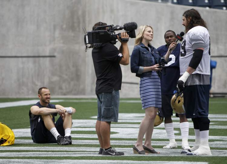 Winnipeg Blue Bombers' Buck Pierce (4) sits and waits to speak with TSN's Sara Orlesky while she interviews Glenn January following practice at Investors Group Field, Sunday, June 9, 2013. 