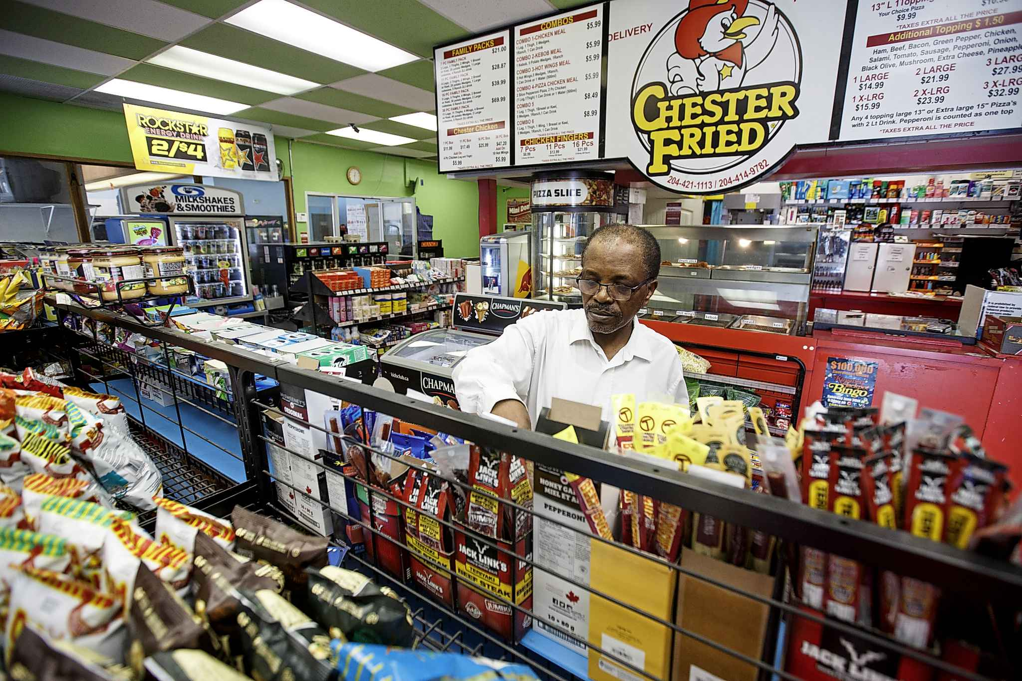 Degu Awegachew organizing stock at Bunty's convenience store which is owned by his son Yonas Zewude.