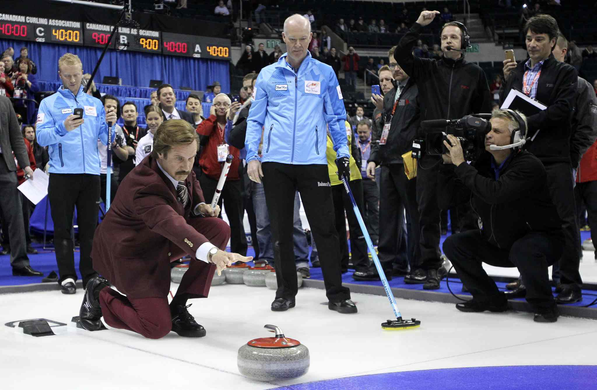 Ron Burgundy, a.k.a. Will Ferrell, throws a rock prior to the Roar of the Rings curling event at the MTS Centre Sunday.