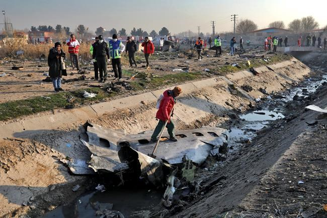 Rescue workers inspect the scene where a Ukrainian plane crashed in Shahedshahr, southwest of the capital Tehran, Iran, Wednesday, Jan. 8, 2020. A Ukrainian airplane with more than 170 people crashed on Wednesday shortly after takeoff from Tehran's main airport, killing all onboard. (AP Photo/Ebrahim Noroozi)