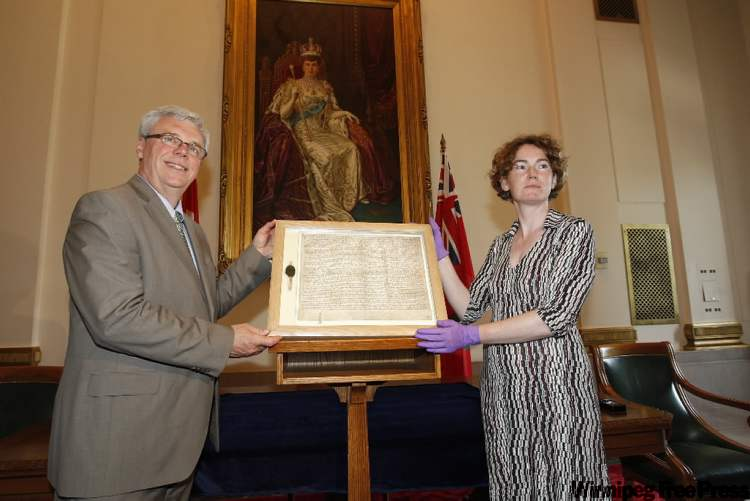 Premier Greg Selinger unveils a copy of the Magna Carta in the Legislative Building today. With the premier is Madeline Slaven, from the University of Oxford, who accompanied the Magna Carta to the city.