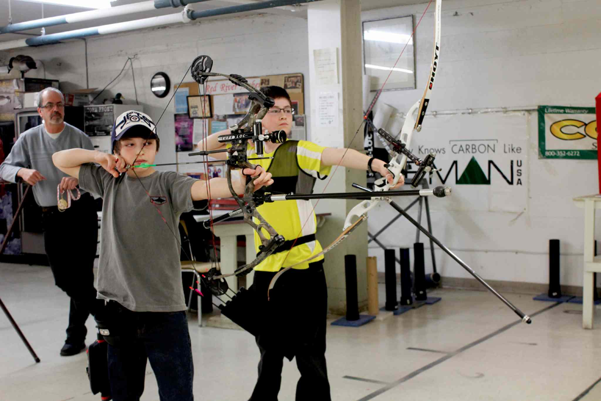 Robbie Comberbach (left) shoots with a compound bow while his friend and fellow archer Riel Lewer (right) shoots with a recurve bow.