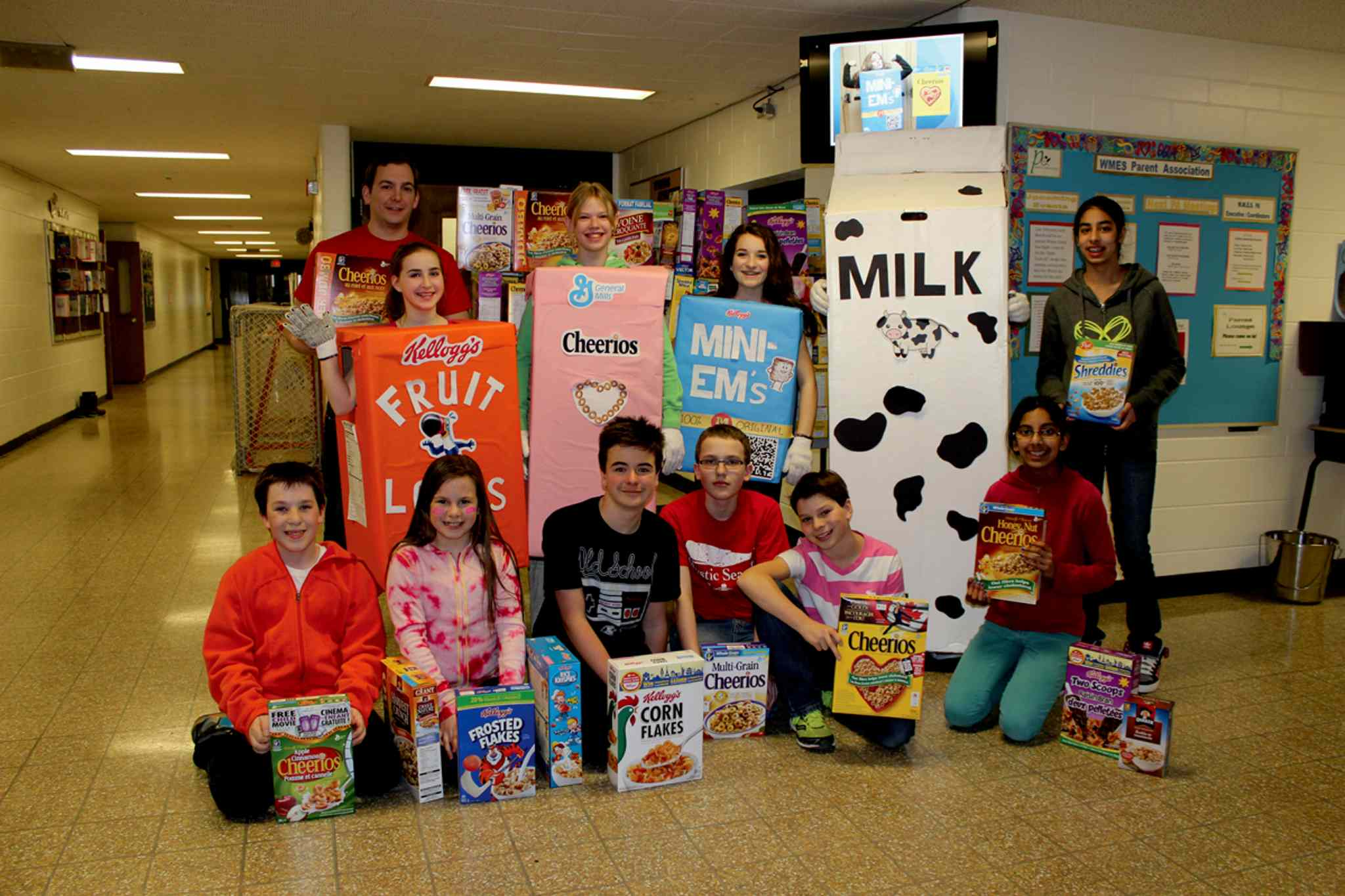 Students and faculty are pictured with some of the donations. Top row: Mr. Thiessen, Sarah Kovacs, Jennifer Einarson, Emma Houldsworth, Tae Yeop Kim (in milk container costume), and Nisha Dhaliwal. Bottom row: Ethan Dyck, Ashley Bull, Ryan Lewis, Ben Ulmer, Braydon Labossiere, and Imtiaz Sidhu.
