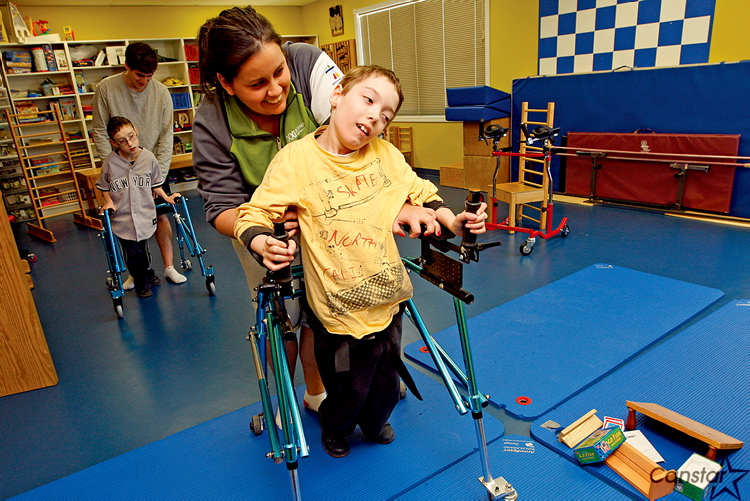 Movement Centre worker Katherine Cobb works with William Lindhorst. The Movement Centre teaches conductive education, a learning system merging education with therapeutic programming.