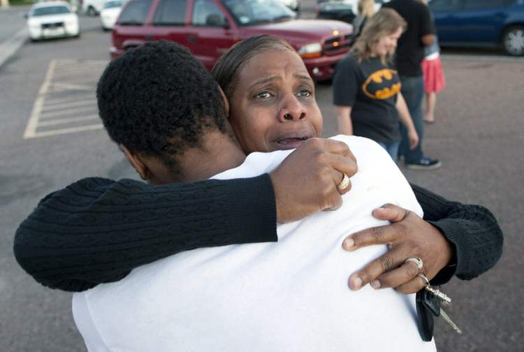"Shamecca Davis hugs her son Isaiah Bow, who was an eye witness to the shooting, outside Gateway High School where witness were brought for questioning Friday, July 20, 2012 in Denver. After leaving the theater Bow went back in to find his girlfriend. "" I didn't want to leave her in there. But she's ok now,"" Bow said. A gunman wearing a gas mask set off an unknown gas and fired into a crowded movie theater at a midnight opening of the Batman movie ""The Dark Knight Rises,"" killing at least 12 people and injuring at least 50 others, authorities said. (AP Photo/Barry Gutierrez) (CP)"